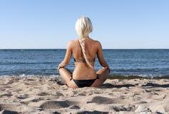Het meisje van de blonde zit op het strand en mediteert royalty-vrije stock afbeelding