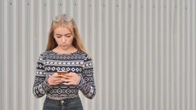 Het meisje van de blondetiener draait het aantal en op de telefoon en de besprekingen stock fotografie