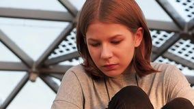 Het meisje van de close-uptiener in een grijs vest met een notitieboekje in haar handen zit in een park onder de koepel kijkt ron stock videobeelden