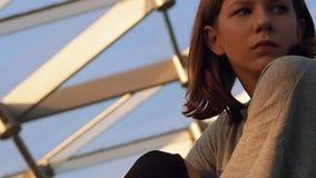 Het meisje van de close-uptiener in een grijs vest zit in een park onder de koepel kijkt rond in de avond in het licht van het pl stock videobeelden