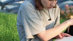 Het meisje van de close-uptiener in een grijze t-shirt zit op het gras in het park kijkt rond en leest een notitieboekje met lezi stock video