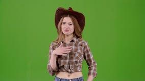 Het meisje van de cowboystijl sluit haar neus, ruikt onplezierig rond haar Het groene scherm stock videobeelden