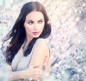 Het meisje van de de lentemanier in bloeiende bomen Royalty-vrije Stock Afbeelding
