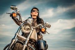 Het meisje van de fietser op een motorfiets royalty-vrije stock afbeeldingen