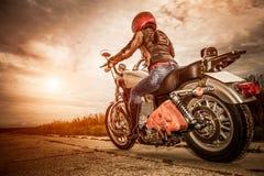 Het meisje van de fietser op een motorfiets Stock Fotografie