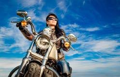 Het meisje van de fietser op een motorfiets stock afbeelding