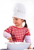 Het meisje van de glimlach in het kokkostuum stock foto's