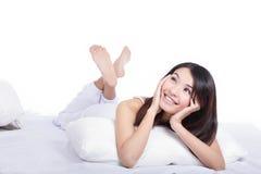 Het meisje van de glimlach het liggen op bed en ziet omhoog eruit vooruit Stock Fotografie
