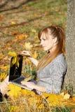 Het meisje van de herfst met laptop stock afbeeldingen