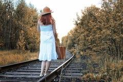 Het meisje van het de herfstpark in witte sundress en het rieten koffer lopen Stock Afbeelding