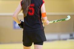 Het meisje van de hockeyspeler met stok in het spel Achter mening stock foto