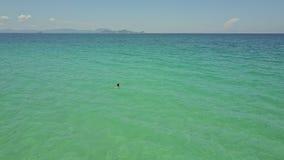Het Meisje van de hommelmening zwemt in Oceaan tegen Verre Heuvels op Horizon stock videobeelden