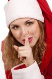 Het meisje van de kerstman met vinger op lippen Stock Foto's