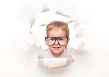 Het meisje van de kindbaby met grappige staarten met glazen die door een gat in Witboek piepen stock foto's