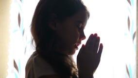 Het meisje van de kindtiener het bidden bidt silhouet in stock videobeelden