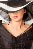 Het meisje van de manier in een grote hoed in de studio Stock Foto's