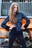 Het meisje van de manier in een jasje naast de bouw stock afbeeldingen