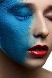 Het meisje van de manierschoonheid met blauwe sneeuw op gezicht stock foto's