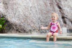 Het meisje van de peuter het bespatten in zwembad Stock Foto's