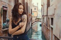 Het meisje van de reistoerist op een brug op een straat in Venetië in het zonlicht stock foto's