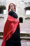 Het meisje van de roodharige binnen met rood satijn Stock Fotografie