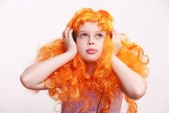 Het meisje van de roodharige luistert aan muziek royalty-vrije stock fotografie