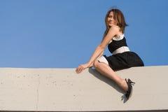 Het meisje van de schoonheid zit op muur Stock Foto's