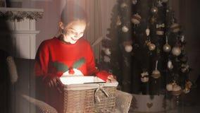 Het meisje van de schoonheidstiener het openen de doos van de Kerstmisgift met mirakellichten stock footage
