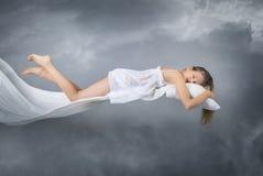 Het meisje van de slaap Het vliegen in een droom Wolken op grijze achtergrond royalty-vrije stock foto's