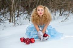 Het Meisje van de sneeuw in een de winterbos met appelen royalty-vrije stock afbeelding
