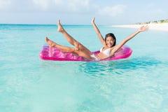 Het meisje van de strandpret speels op oceaanvlottermatras stock afbeelding