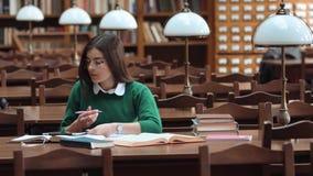 Het meisje van de student in bibliotheek stock footage