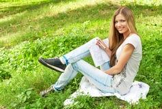 Het meisje van de student op het gras Stock Afbeeldingen