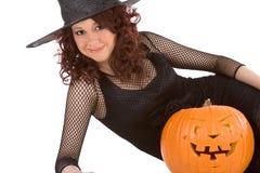 Het meisje van de tiener in de hoed van Halloween met gesneden pompoen stock foto's