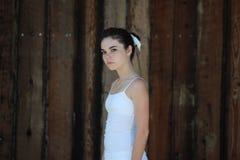 Het meisje van de tiener door bruine houten achtergrond Stock Foto