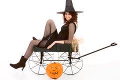 Het meisje van de tiener in het kostuum van Halloween op kar door pompoen royalty-vrije stock fotografie