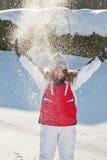 Het meisje van de tiener het spelen met sneeuw in park stock foto