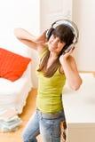 Het meisje van de tiener ontspant gelukkig huis - luister aan muziek royalty-vrije stock fotografie