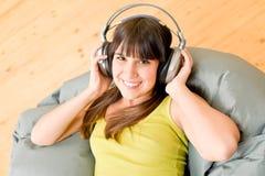Het meisje van de tiener ontspant gelukkig huis - luister aan muziek royalty-vrije stock afbeeldingen