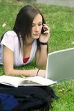 Het meisje van de tiener op de telefoon die op het gras bepaalt royalty-vrije stock foto