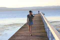 Het meisje van de tiener op houten voetgangersbrug bij meer Royalty-vrije Stock Foto's