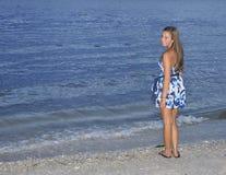 Het meisje van de tiener op strand bij schemer Stock Foto