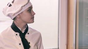 Het meisje van de tienerkok in een keuken stock videobeelden
