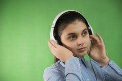 Het meisje van de tienerschool luistert muziek in hoofdtelefoons Stock Foto