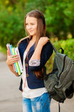 Het meisje van de tienerstudent met boeken en een rugzak in handen Royalty-vrije Stock Afbeeldingen