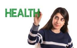 Het meisje van de tieneruniversiteit het schrijven gezondheid op het transparante scherm stock foto