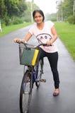 Het meisje van de universiteit op haar cyclus, bij het midden van weg. Stock Afbeeldingen