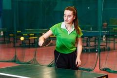 Het meisje van de vijftien éénjarigentiener in het groene speelpingpong van de sportent-shirt stock foto