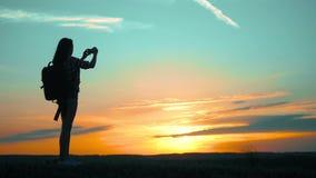 Het meisje van het de wandelaarsilhouet van silhouethipster schiet video van mooie aardzonsondergang op langzame smartphone van d stock videobeelden