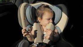 Het meisje van de zuigelingsbaby in autozetel stock videobeelden